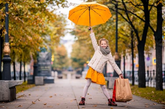Garota feliz fica em uma rua de cidade de outono com sacolas de compras e um guarda-chuva amarelo brilhante.