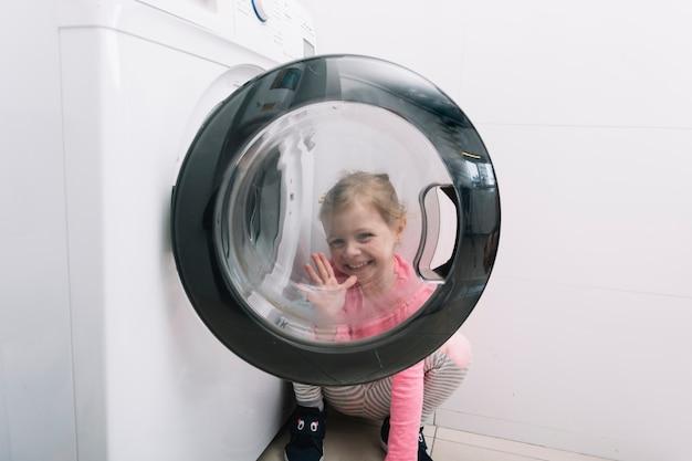 Garota feliz gesticulando pela porta da máquina de lavar roupa