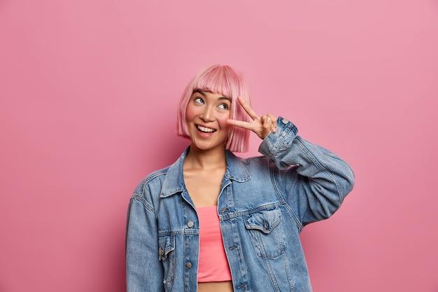 Garota feliz hipster de cabelo rosa faz gesto de victroy, sorri e se alegra com sucesso, expressa visão positiva, tem expressão sonhadora, vestida com roupas da moda. mulher estilosa fazendo sinal de v com os dedos