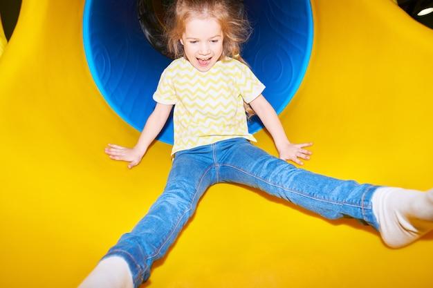 Garota feliz indo para baixo slide