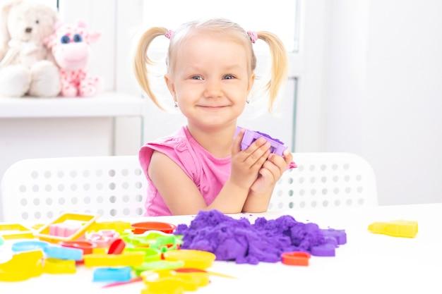 Garota feliz joga areia cinética em quarentena. a menina bonita loura sorri e joga com areia roxa em uma tabela branca.