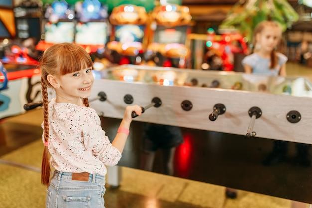 Garota feliz jogando futebol de mesa no centro de jogos infantis