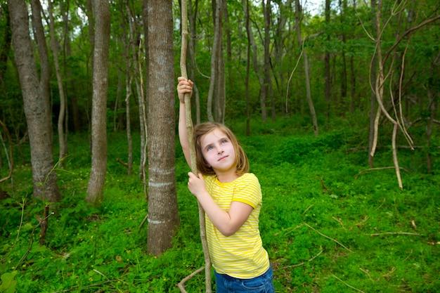 Garota feliz jogando na floresta forest park com liana