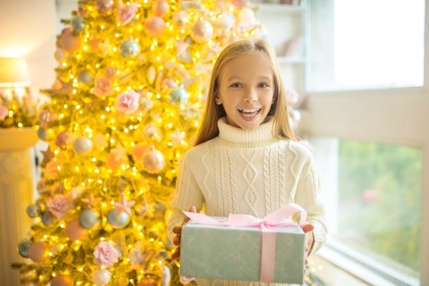 Garota feliz. linda garota segurando presentes de natal e parecendo feliz