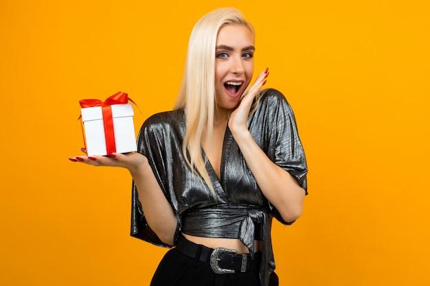 Garota feliz mantém um presente em uma parede isolada em amarelo