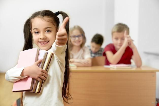 Garota feliz, mantendo os livros e mostrando sinal ok em pé