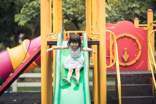 Garota feliz na área de recreio slide