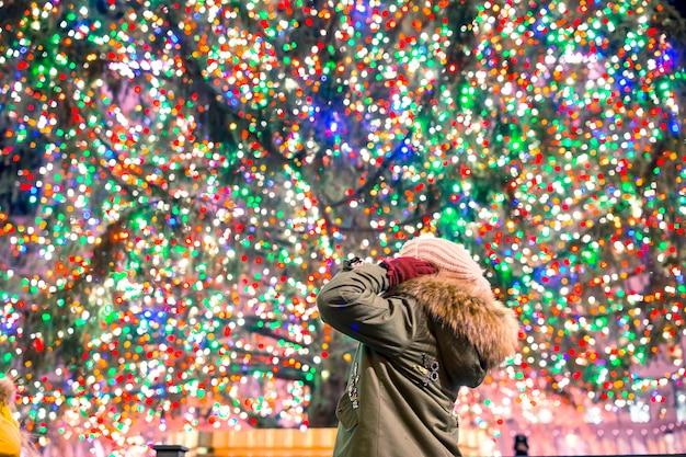 Garota feliz na árvore de natal rockefeller em nova york