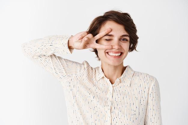 Garota feliz na blusa mostrando sinal de paz ou vitória no olho e piscando, expressa positividade e alegria, em pé contra uma parede branca