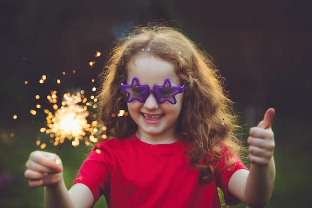 Garota feliz na festa com queima de diamante na mão.