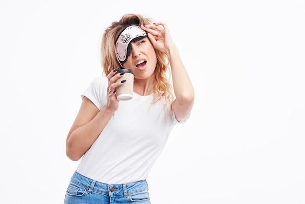 Garota feliz na máscara de dormir e pijama branco acordou de manhã cedo e olhando para a câmera e sorrindo.