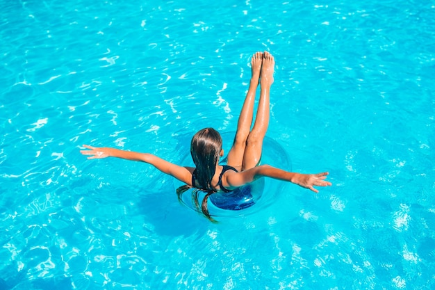 Garota feliz na piscina ao ar livre, nadar e relaxar