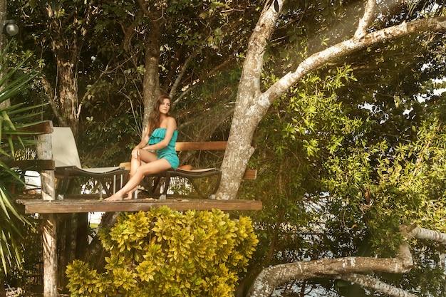 Garota feliz na plataforma na árvore com espreguiçadeiras