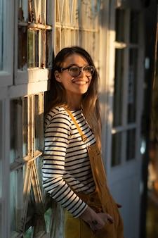 Garota feliz na postura geral na parede da estufa sorrindo