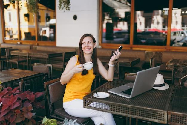 Garota feliz na rua ao ar livre, café, café, sentado à mesa com o computador laptop pc, mensagem de texto no celular, beber uma xícara de chá no restaurante durante o tempo livre