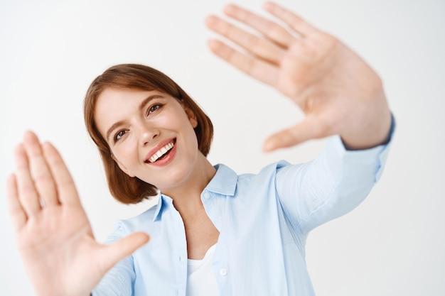 Garota feliz natural com cabelo curto, sonhando, estique as mãos, capture e aproveite o momento, em pé na parede branca