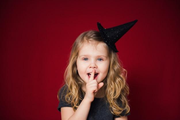 Garota feliz no chapéu de bruxa em fundo vermelho