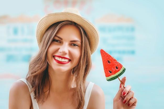 Garota feliz no chapéu de palha com um pirulito e batom vermelho, sorrindo em uma parede azul. linda garota cobre os olhos com pirulito tolos e ri. garota turista se divertindo no verão