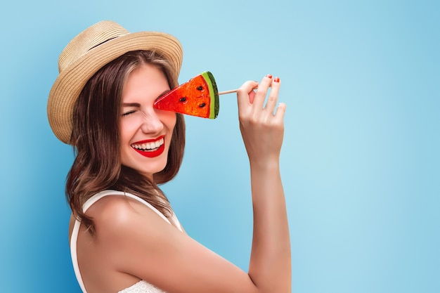 Garota feliz no chapéu de palha com um pirulito e batom vermelho, sorrindo em uma parede rosa. linda garota cobre os olhos com pirulito tolos e ri. garota turista se divertindo no verão