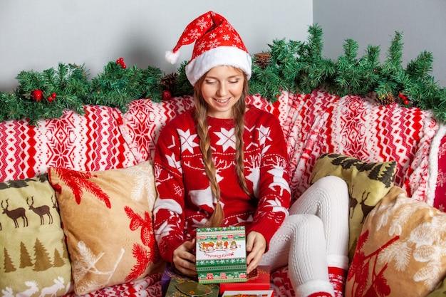 Garota feliz no chapéu de papai noel abre uma caixa de presente de natal com presente dentro