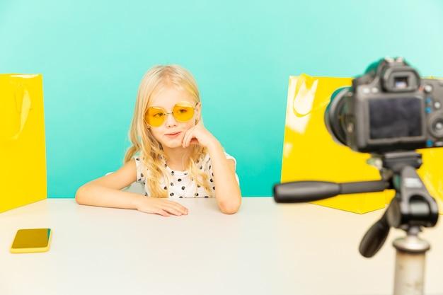 Garota feliz no estúdio azul, falando na frente da câmera para o vlog. trabalho como blogger, gravando vídeo tutorial para internet.