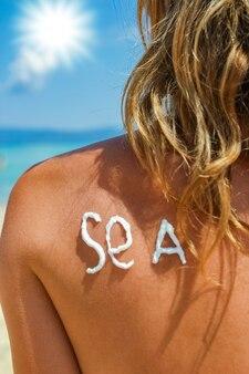 Garota feliz no mar com uma foto do sol nas costas