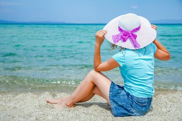 Garota feliz no mar na grécia, na natureza de areia