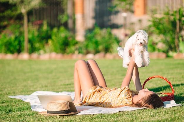 Garota feliz no piquenique brinca com cachorro branco na grama verde do parque