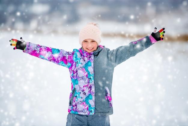Garota feliz no terno de esqui ao ar livre