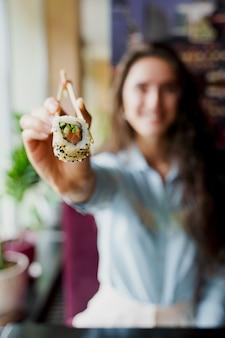 Garota feliz oferecendo sushi em restaurante japonês