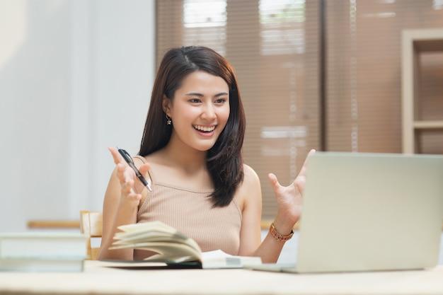 Garota feliz olha para ouvir a tela do computador e aprender cursos on-line no apartamento com videochamada