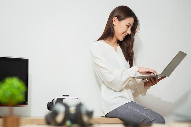 Garota feliz olhando para a tela do computador, ouvindo e aprendendo cursos on-line em um apartamento com videochamada