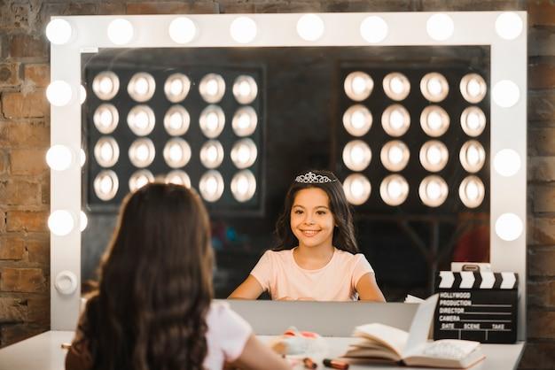 Garota feliz olhando seu reflexo no espelho no backstage