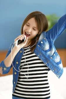 Garota feliz ouvindo música e cantando no celular interno