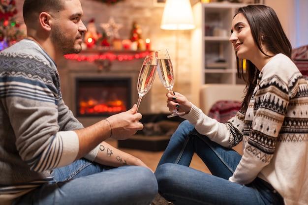 Garota feliz pensando o quanto ela ama o namorado no dia de natal, tilintando uma taça de champanhe.