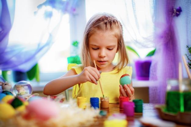 Garota feliz pintando ovos de páscoa, criança pequena em casa se divertir. feriado de primavera