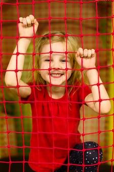 Garota feliz posando atrás da rede