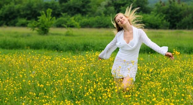 Garota feliz posando com as mãos ao alto em um campo de flores amarelas. jovem loira com um vestido de renda branca