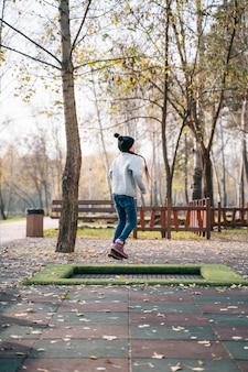 Garota feliz pulando de um pequeno trampolim no parque
