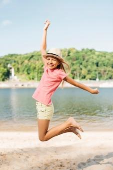 Garota feliz pulando na areia