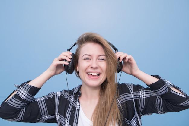 Garota feliz que ouve música em fones de ouvido em um fundo azul, olha para a câmera e sorri.