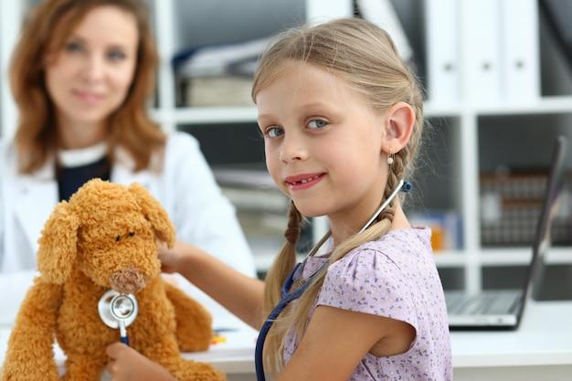Garota feliz se divertindo com ursinho de pelúcia no médico