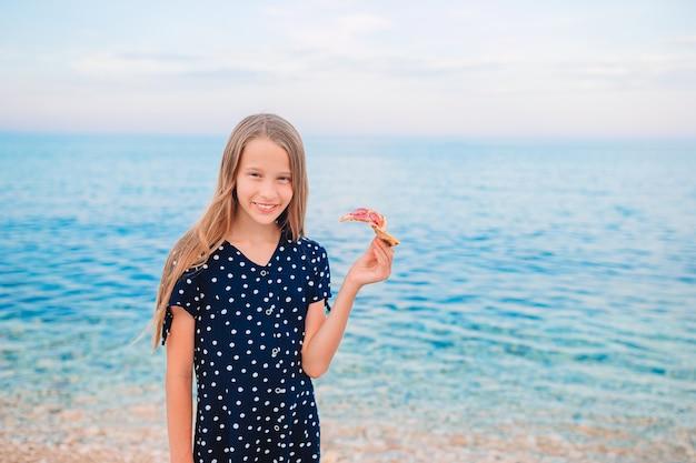 Garota feliz se divertindo na praia e comendo pizza