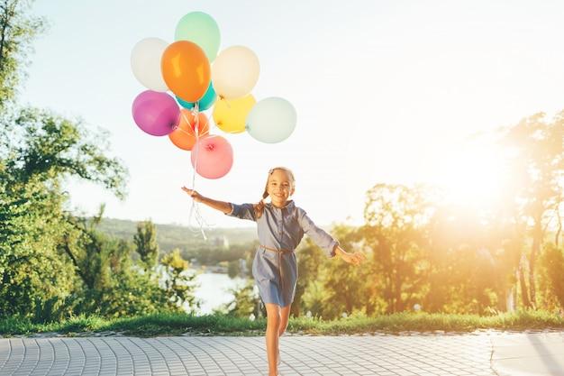 Garota feliz, segurando balões coloridos no parque da cidade