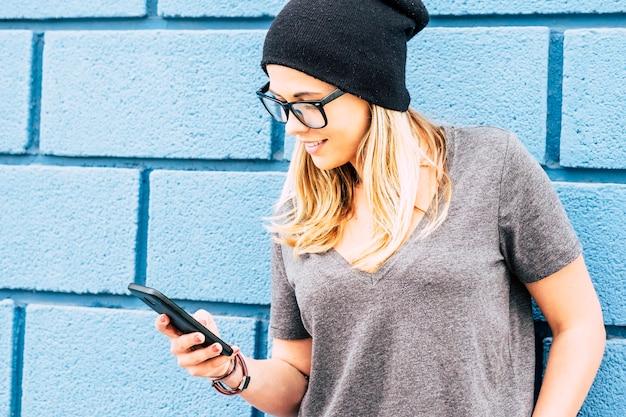 Garota feliz segurando e usando seu smartphone sozinha - mulher caucasiana brincando com seu telefone - anos 20 anos com óculos