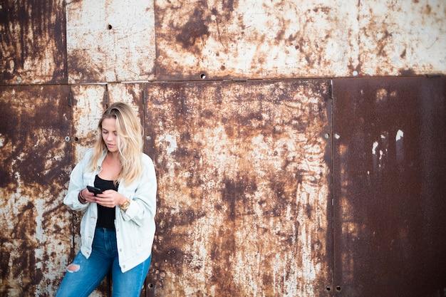 Garota feliz segurando e usando seu smartphone sozinha - mulher caucasiana brincando com seu telefone - anos 20 milenares - pessoas