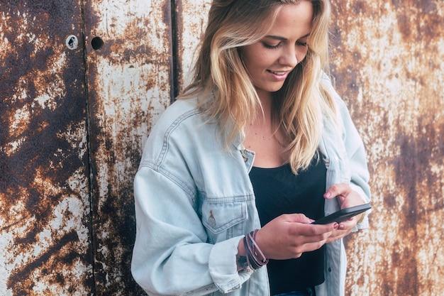 Garota feliz segurando e usando seu smartphone sozinha - mulher caucasiana brincando com seu telefone - anos 20 milenares