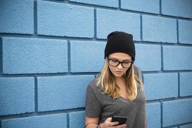 Garota feliz segurando e usando seu telefone inteligente sozinha - mulher caucasiana brincando com seu celular - milenar 20 anos com óculos e chapéu preto em local urbano