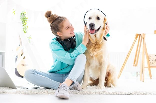 Garota feliz segurando fones de ouvido na cabeça de cachorro, sentada no chão em uma sala iluminada