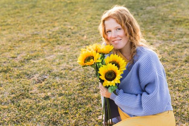 Garota feliz, segurando girassóis